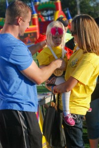 Emma getting her medal from Olympian Curt Tomasevicz at the Glow Gold event.