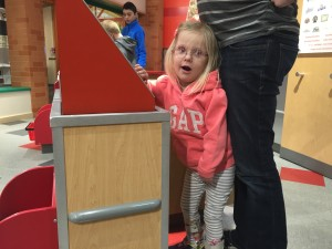 Emma was being a cashier and really happy about it.